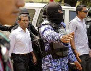 Former Maldives President Mohamed Nasheed is escorted by police officers after being arrested in Male