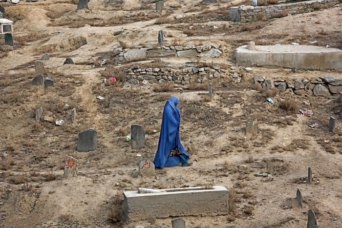 Une femme marche dans un cimetière à Kaboul
